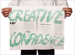 a man holding up a paper, and written on in in green, are the words creative confidence