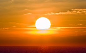 getting out of a sales slump is like this picture of the sun rising over the ocean and the sky is yellow
