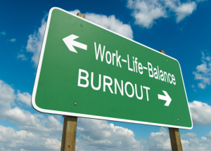 A hi way sign which is green and has the caption that says Work-life-balance with an arrow pointing one way, and another caption that says burnout with an arrow pointing the other way.