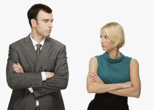 a man and women standing side by side with their arms crossed and they are looking at each other. They are certainly not building rapport in sales.